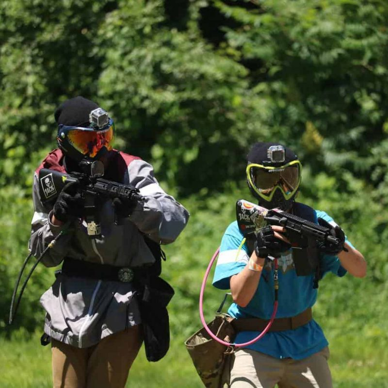 two boys playing paintball at youth group event