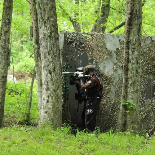 paintball player behind tree on far field